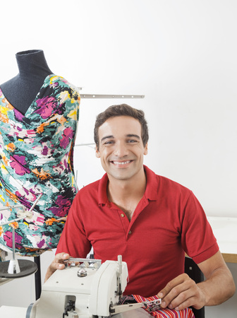 modiste: Portrait of happy young male tailor sitting by mannequin in sewing factory Stock Photo