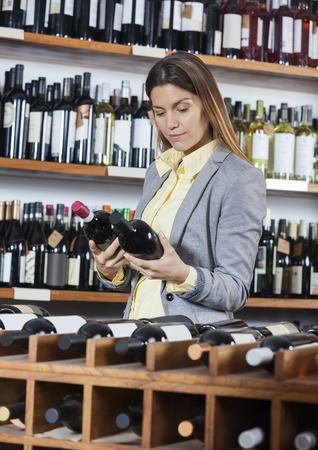 waistup: Mid adult woman looking at wine bottles in store