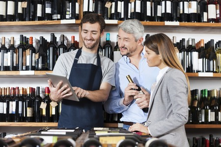 store keeper: Smiling young salesman showing wine information to couple on digital tablet in shop