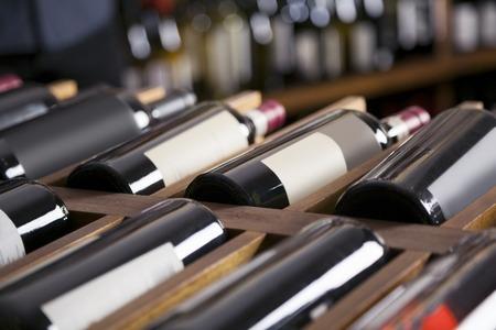 Red wine bottles displayed on shelves in supermarket Standard-Bild