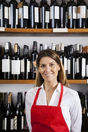 Portrait of confident mid adult saleswoman standing against shelves in wine shop