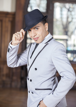 Side view portrait of confident man holding hat while performing tango in restaurant