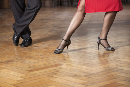Low section of tango professionals performing on hardwood floor in cafe Foto de archivo