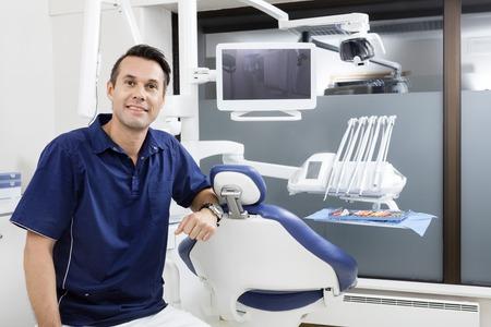 Portrait of zuversichtlich männlichen Zahnarzt von Stuhl an der Klinik
