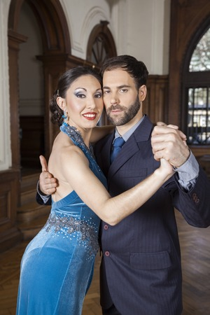 cheek to cheek: Portrait of confident mid adult tango dancers with cheek to cheek performing in restaurant