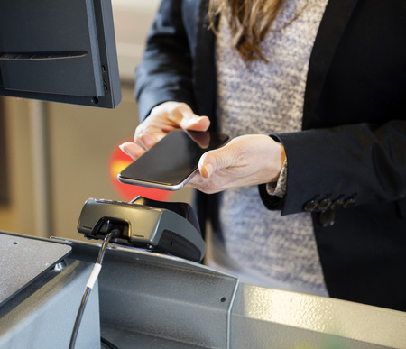 checkout counter: Midsection of female customer doing NFC payment at checkout counter in supermarket Stock Photo