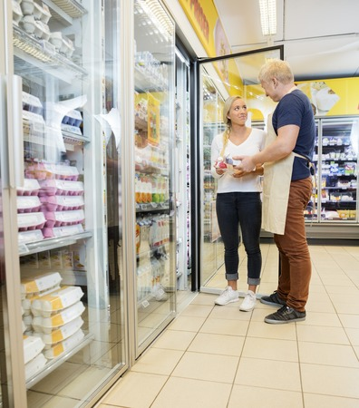 help section: Full length of salesman showing products to customer in grocery store