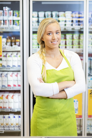 Portrait of confident female worker standing arms crossed in grocery store