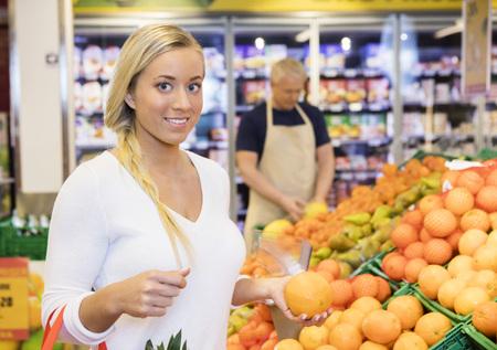 Portrait of confident female customer holding orange in supermarket