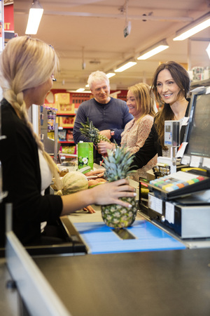 checkout counter: Female cashier making bills while customers standing at checkout counter in supermarket