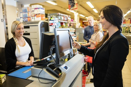 Smiling cashier looking at female customer making NFC payment at checkout counter in grocery store Stok Fotoğraf