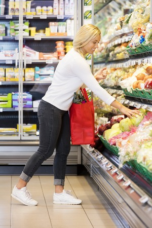 buying: Woman Buying Cabbage In Supermarket