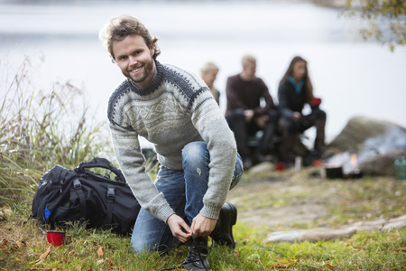 staycation: Hiking Male Tying Shoelace With Friends In Background Stock Photo