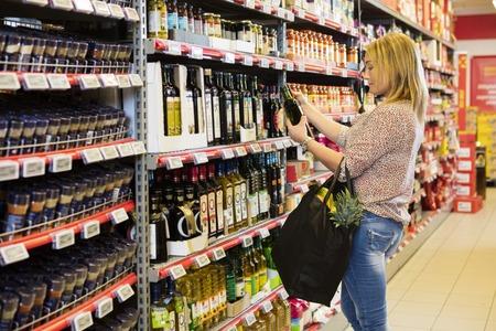 スーパー マーケットのオリーブ オイルのボトルを保持している女性