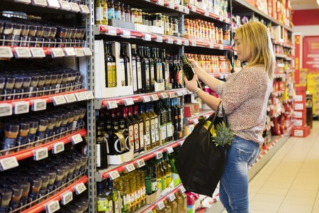 Woman Holding Olive Oil Bottle In Supermarket