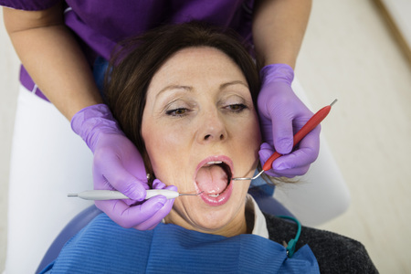 scaler: Patient With Mouth Open Being Examined By Dentist Holding Tools