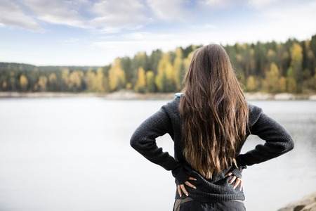 staycation: Rear View Of Woman With Hands On Hips Standing By Lake Stock Photo