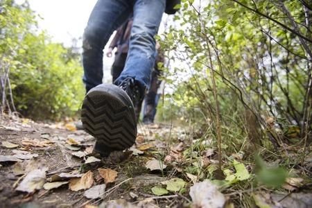 Hombre que usa los zapatos mientras que camina en rastro del bosque