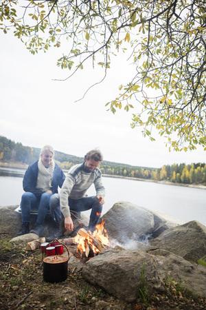 campsite: Couple Sitting Near Bonfire On Lakeshore