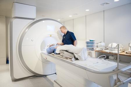 Médico que pone la bobina en la cabeza femenina de los pacientes que se somete a la exploración de la resonancia magnética