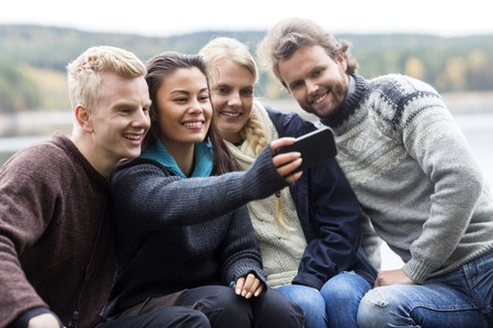 campsite: Friends Taking Selfie With Smartphone At Campsite