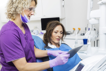 Assistant Showing Report To Patient On Digital Tablet In Dentist Stock Photo