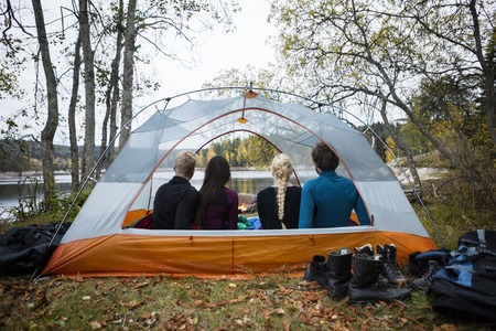 staycation: Young Friends Sitting In Tent On Lakeshore