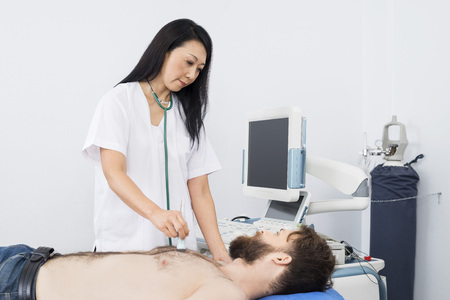 Doctor que examina al paciente con la máquina de ultrasonido