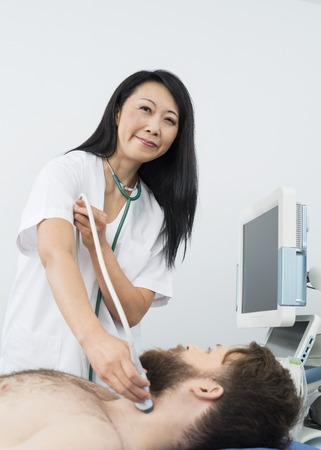 Smiling Doctor Performing Thyroid Ultrasound Test On Patient