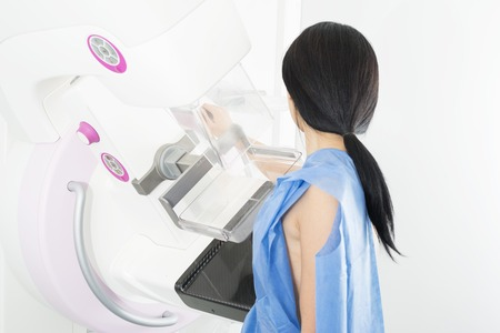 Side View Of Woman Undergoing Mammogram X-ray Test