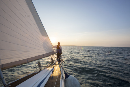 bow of boat: Man Looking At Beautiful Sea From Bow Of Sail Boat