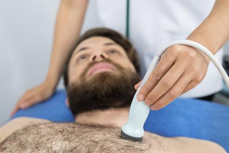 Doctor colocando sonda de ultrasonido en el pecho de pacientes masculinos