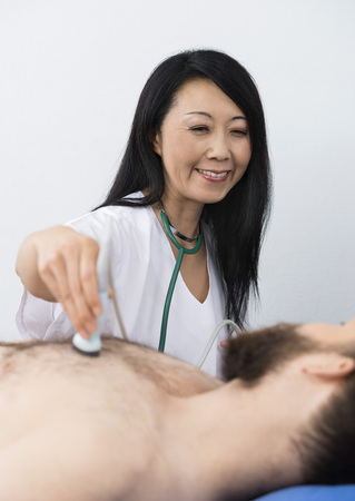 Happy Doctor Performing Ultrasound Treatment On Patient Stock Photo