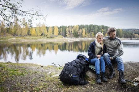 Couple With Backpack Relaxing On Lakeshore During Camping