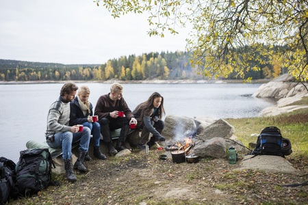 staycation: Friends Having Coffee While Woman Cooking On Campfire Stock Photo