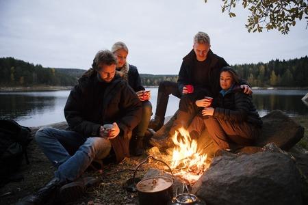 모닥불 근처에 앉아있는 커피 잔을 가진 젊은 친구