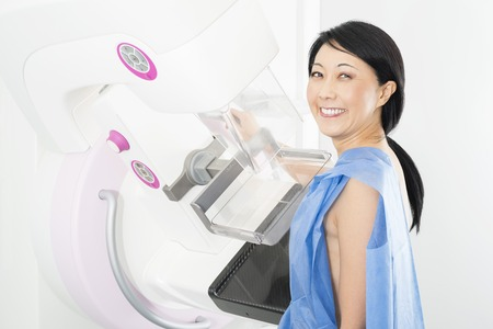 Portrait Of Happy Mature Woman Undergoing Mammogram X-ray Test