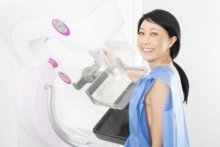 Portrait Of Happy Mature Woman Undergoing Mammogram X-ray Test