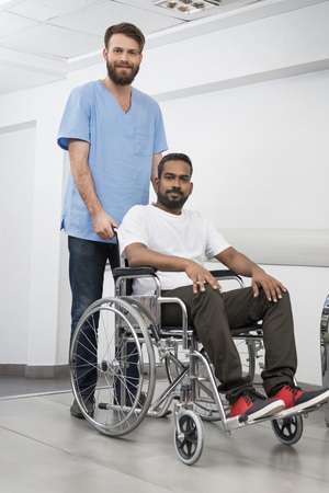 Patient Sitting In Wheelchair While Nurse Standing At Hospital Stock Photo