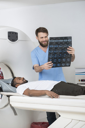 axial: Radiologist Holding X-ray Report While Patient Lying On CT Scann Stock Photo