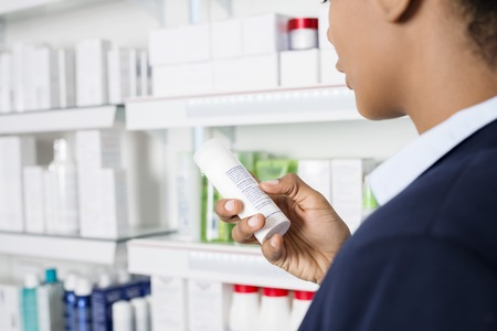 Businesswoman Reading Instructions Medicine Bottle At Pharmacy