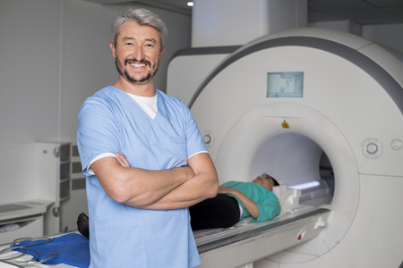 resonancia magnetica: Doctor With Arms Crossed While Patient On CT Scan Machine