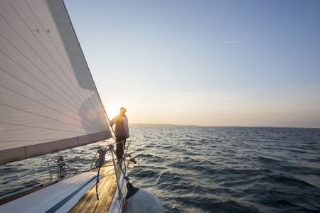 ship bow: Man Standing On Front Of Luxury Yacht In Sea Stock Photo