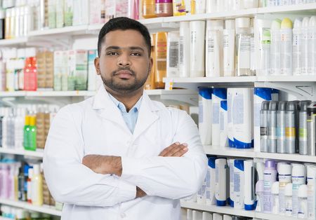 Pharmacist Standing Arms Crossed Against Shelves In Drugstore Stock Photo