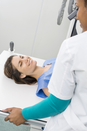 gurney: Radiologist Preparing Female Patient For X-ray In Hospital Stock Photo