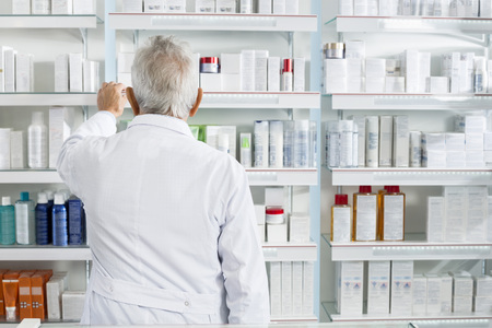 Chemist Searching Medicines In Shelves At Pharmacy Stock Photo