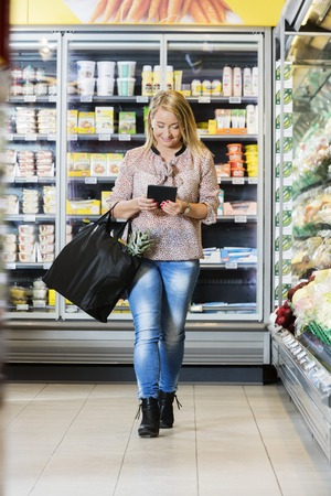 Mature Woman Using Digital Tablet While Walking In Supermarket Archivio Fotografico