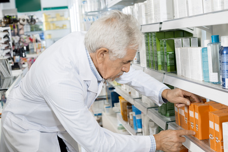 Male Pharmacist Arranging Medicines On Shelf In Pharmacy