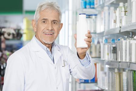 Male Pharmacist Holding Shampoo Bottle In Pharmacy