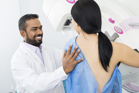 Smiling Doctor Assisting Woman Undergoing Mammogram X-ray Test Stock Photo
